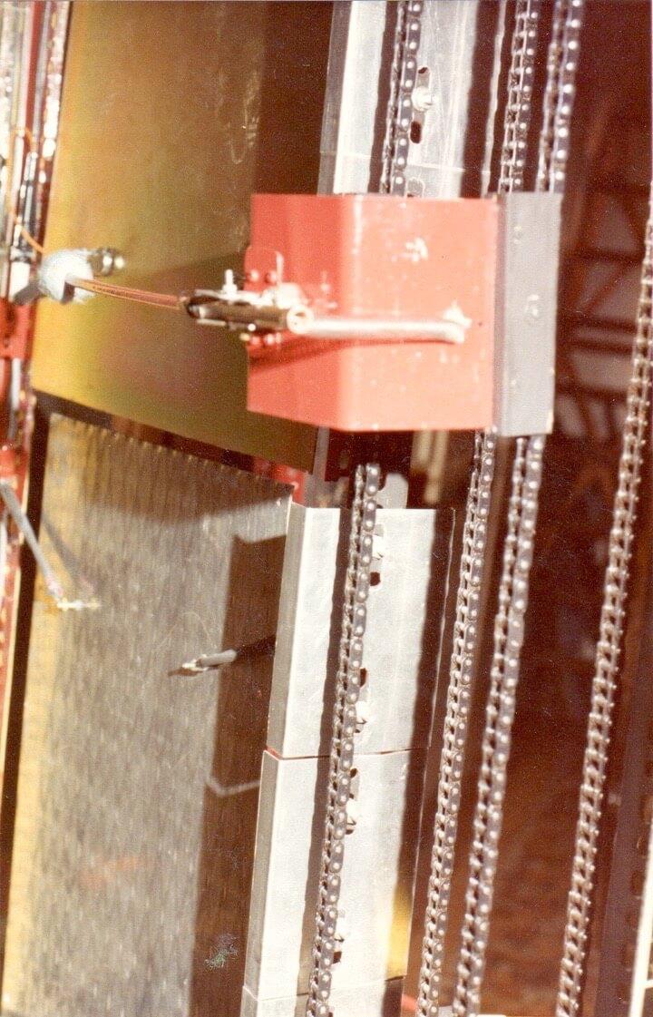Bombyx : transportée par un convoyeur à chaîne vertical une baguette de la Tour à Percussions, sur un support en tôle rouge qui contient l'actionneur