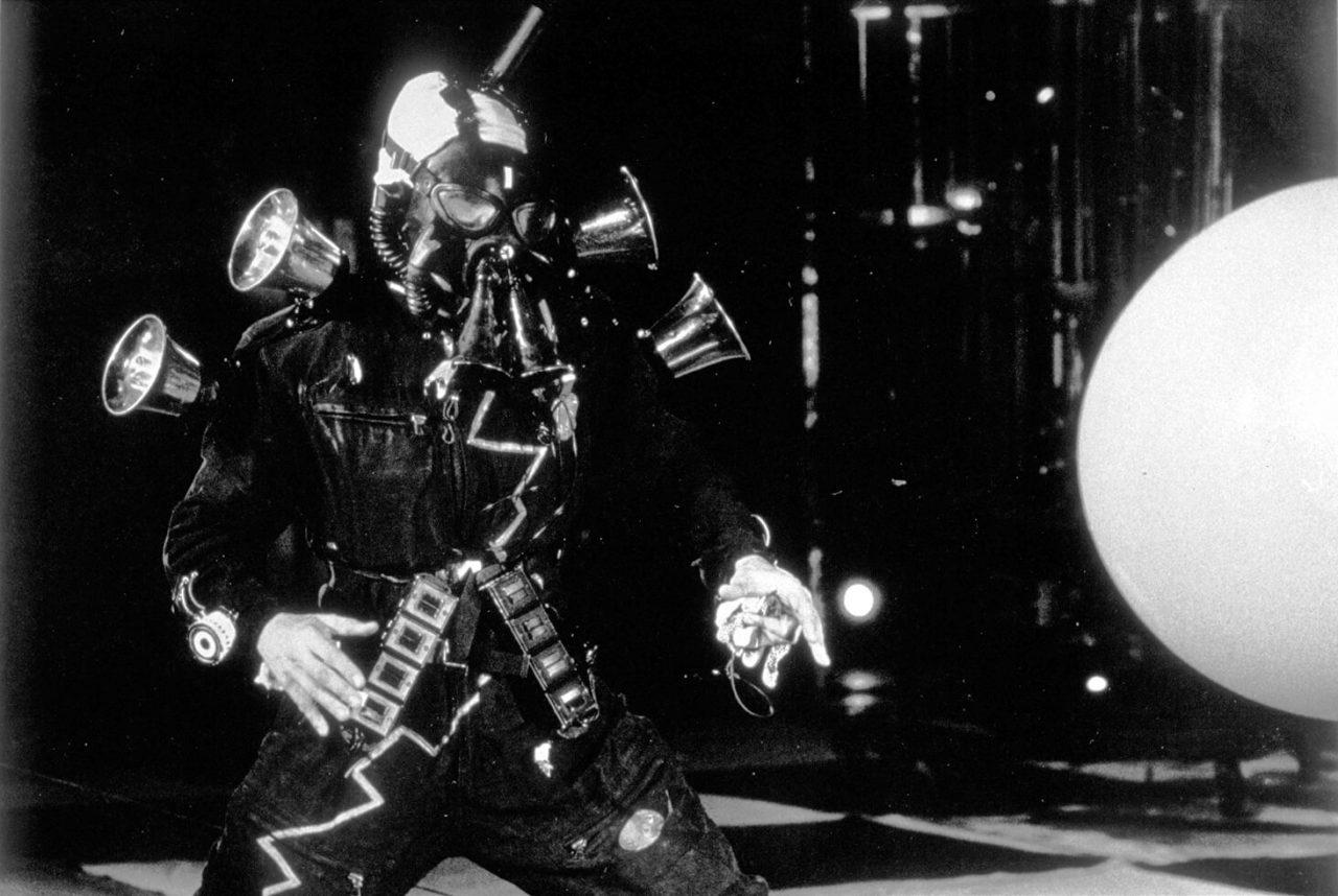 Bombyx, Jacques Rémus à genoux, dans son costume noir avec masque à gaz affronte la machine à Ballon qui s'avance vers lui
