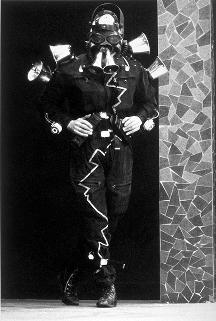 Bombyx , Jacques Rémus debout dans son costume noir avec masque à gaz à double tuyau et sirènes