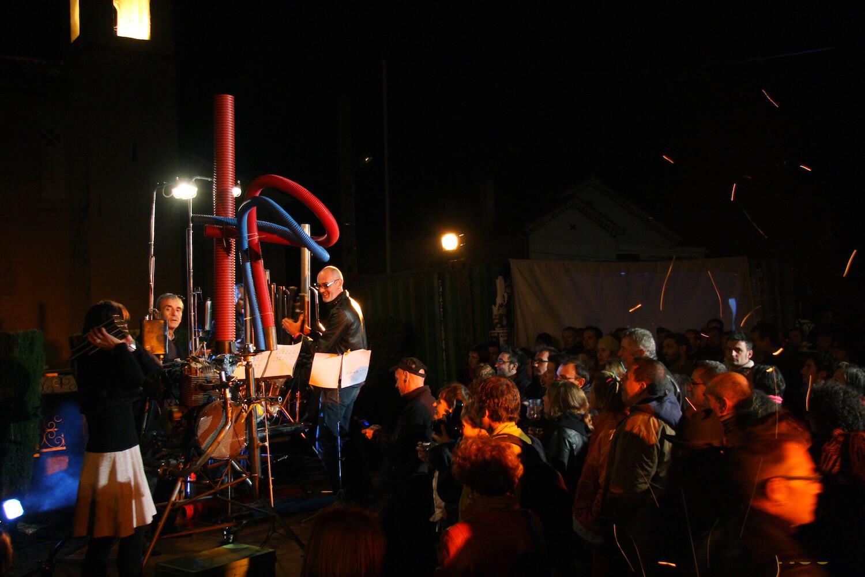 Motorgs : spectacle de nuit, musiciens agglutinés autour des Motorgs et public sur la droite, fond noir