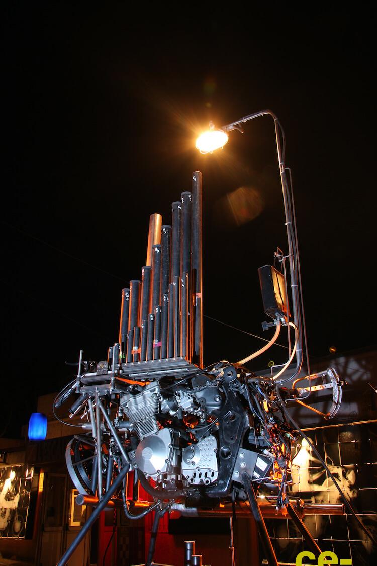 Motorgs : moteur de motocyclette sur pieds avec eux rangées de tuyaux en acier alignés comme deux jeux d'orgue, lumière d'éclairage et manette de commande, sur fond de ciel nocturne