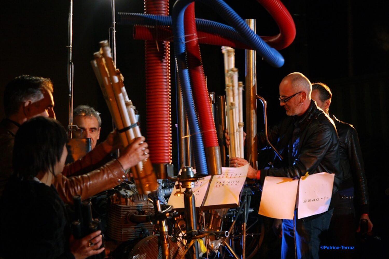 Motorgs : concert de nuit, tuyaux rouges, bleus et gris dont groupés manipulés devant les échappements libres, partitions sur les pupitres