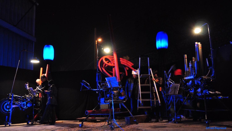 Motorgs :de nuit, avec lumières de spectacle blanche et bleues, 3 Motorgs espacés entourés des musiciens