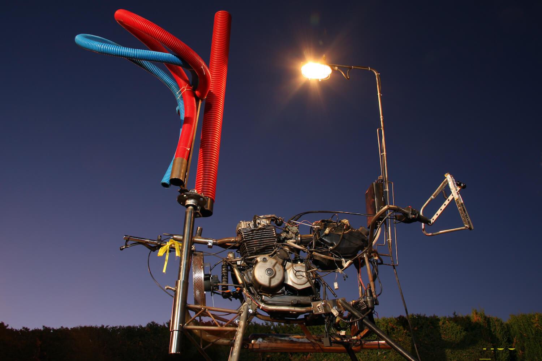 Photographie : moteur de motocyclette sur pieds avec 3 tuyaux rouges et bleu, lumière d'éclairage et manette de commande, sur fond de ciel nocturne