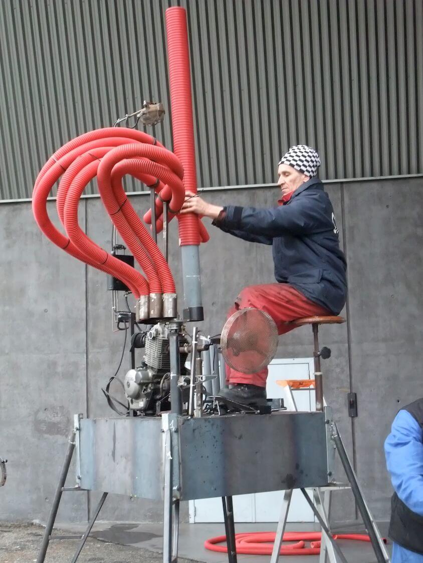 Motorgs : huché sur sa plateforme la machine à tuyaux rouge est manipulée par musicien à bonnet à damier noir et blanc