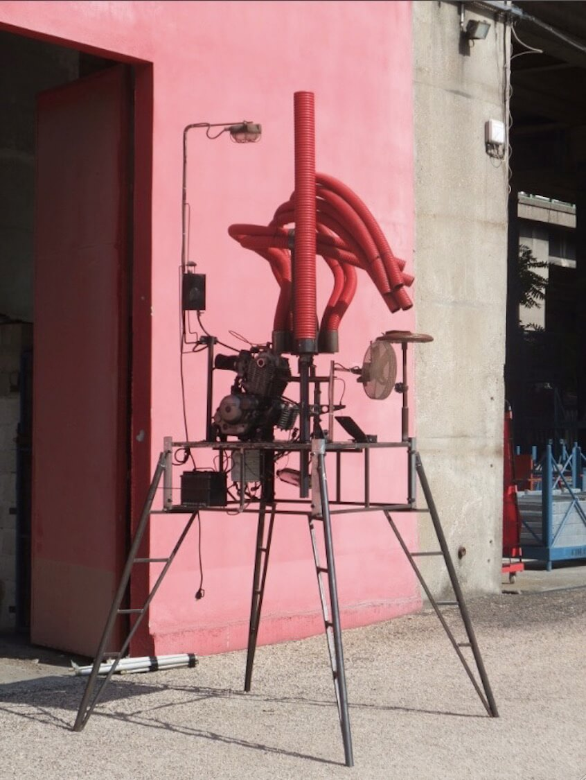 Motorgs sur pieds élégants,avec son lampadaire, son bidon d'essence, devant un mur rose