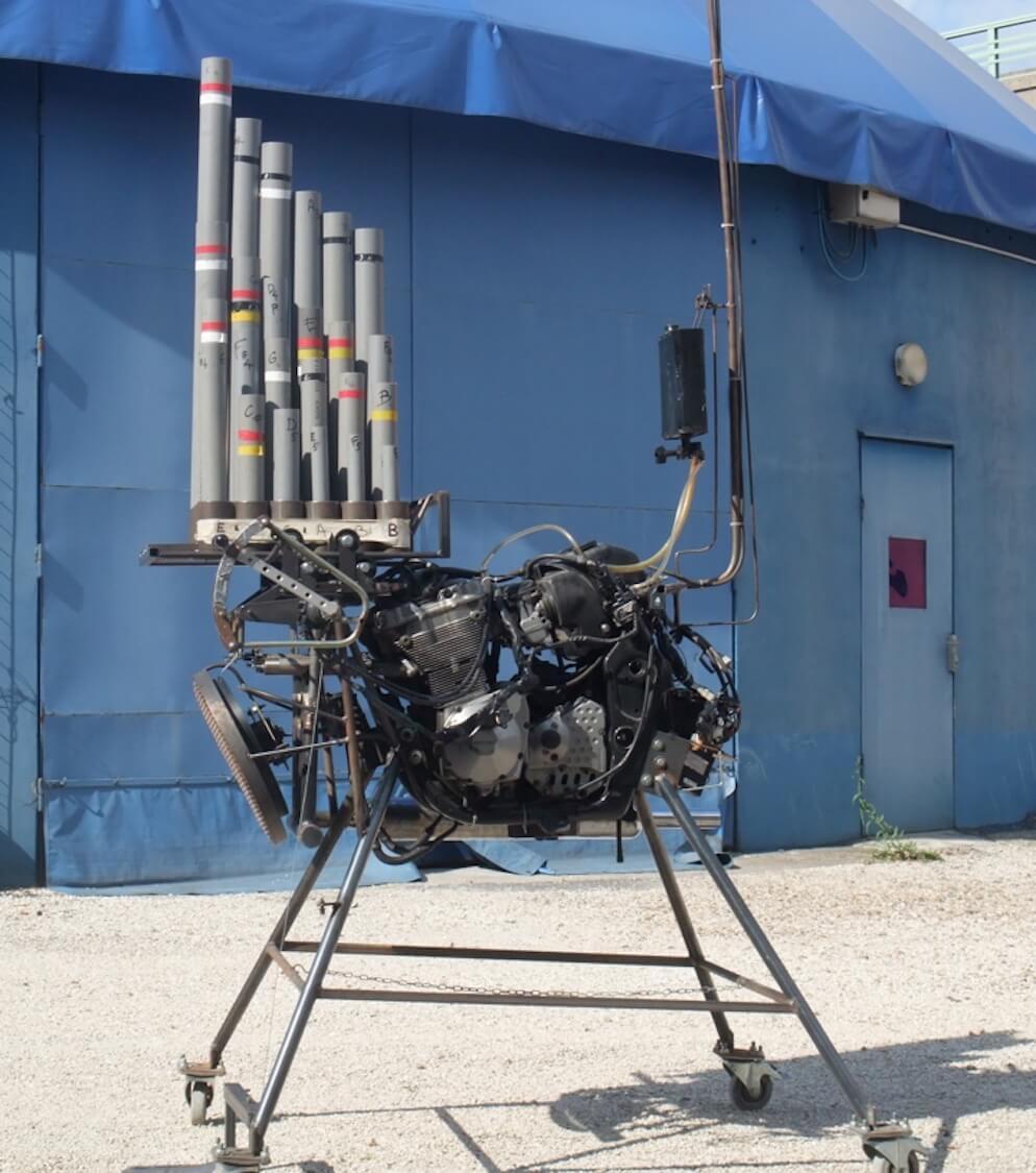 Motorgs sur pieds ,avec son bidon d'essence, sur sol gris, devant la paroi bleue d'un chapiteau