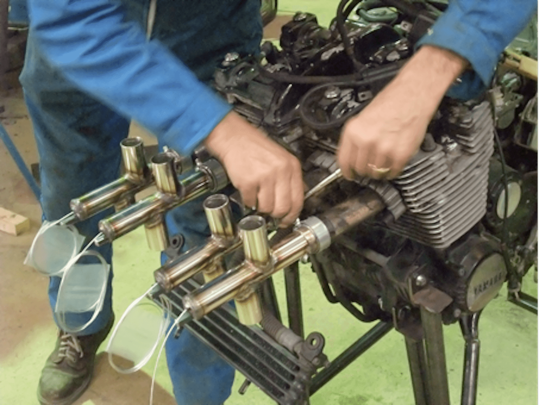 Motorgs : gros plan sur échappements moteur avec 2 mains technicien en combinaison bleue tenant un outil