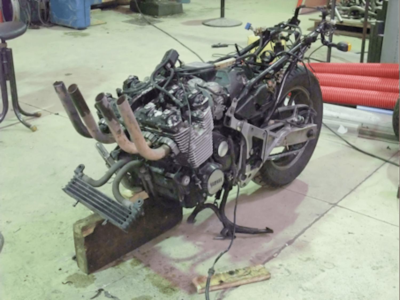 Motorgs : sur le sol de l'atelier il ne reste que le moteur et la partie arrière d'une grosse 4 cylindres dont les échappements sont tournés vers le ciel