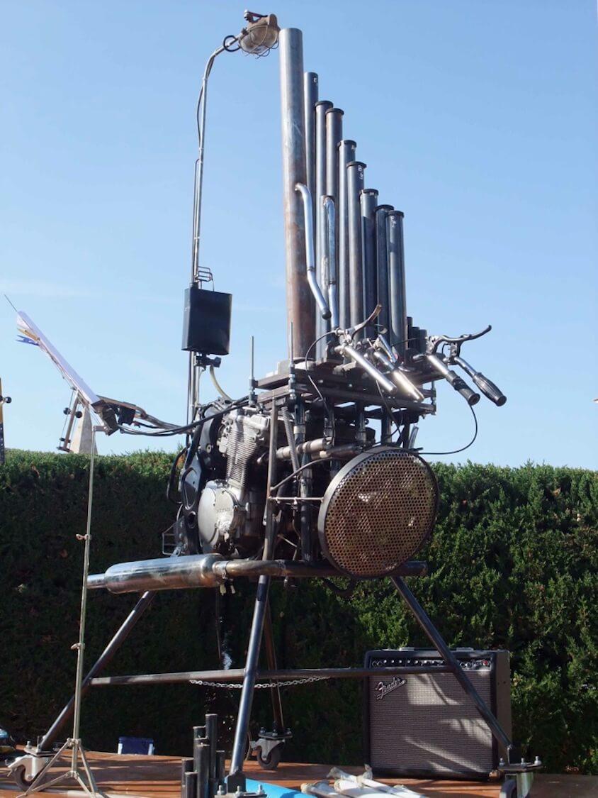 Motorgs : instrument à tuyaux d'acier coulissants, disposés comme un jeu d'orgue sur fond de haie et ciel bleu