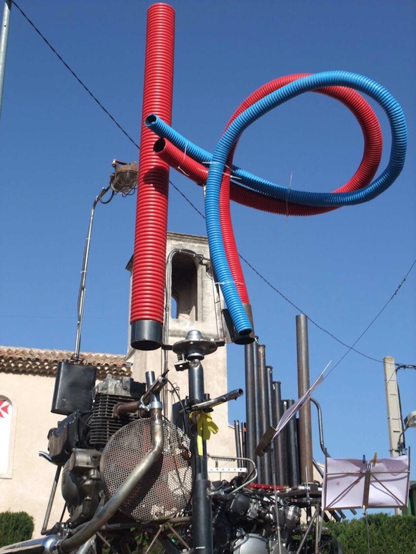 Motorgs :tuyaux rouges et bleu, tuyaux acier au deuxième plan sur fond de vielle église et de ciel bleu