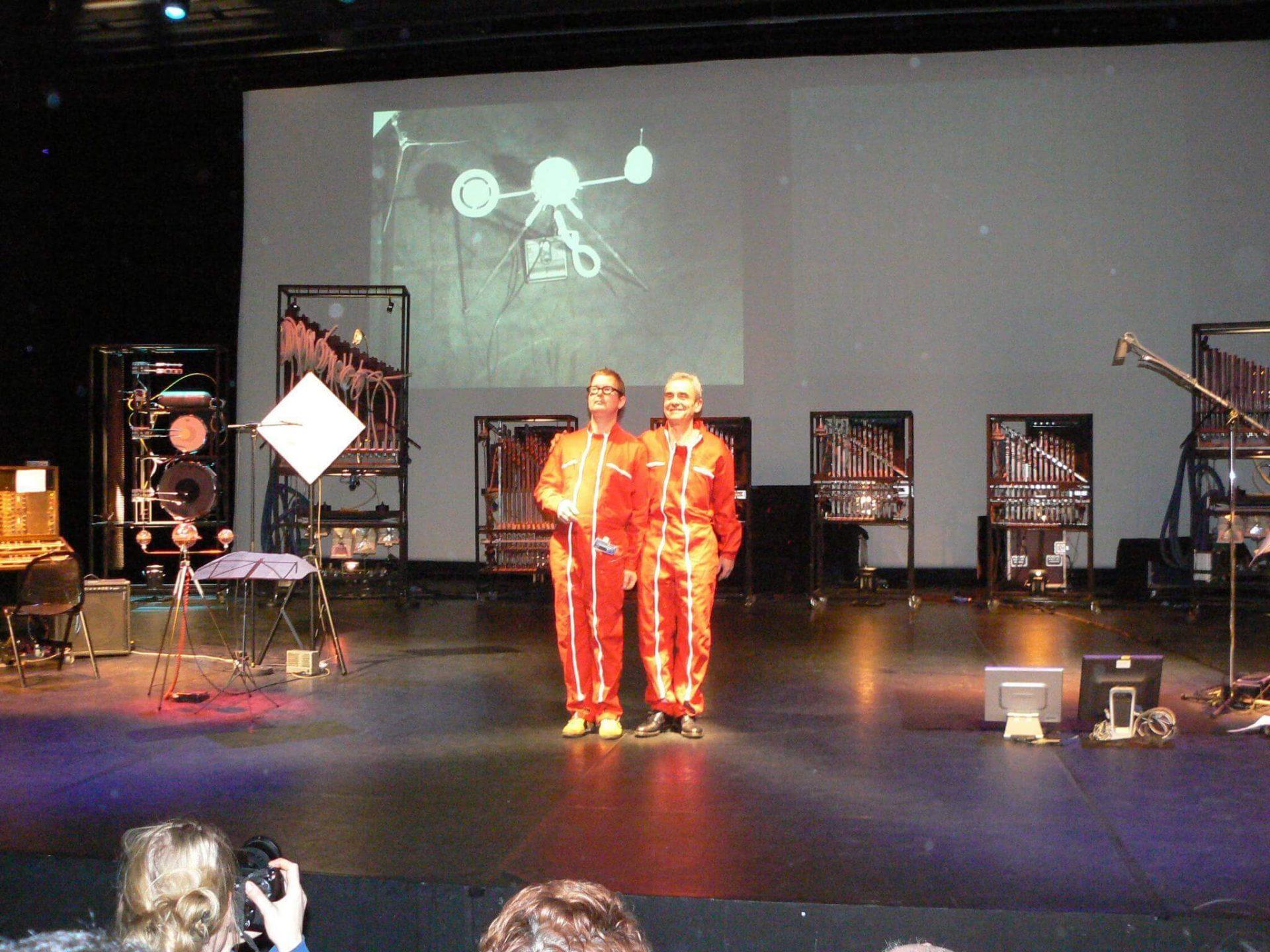 Photographie: scène avec deux musiciens en combinaison rouge saluent le public devant les machines de Jacques Rémus