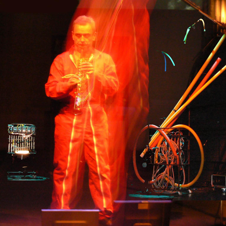Photographie: scène avec un musicien en combinaison rouge devant les machines Mécamusique. Effet lumineux de spectacle