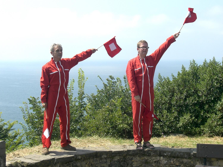 Photographie: deux hommes en combinaison rouge manient des drapeaux en haut d'une falaise, océan en arrière plan.