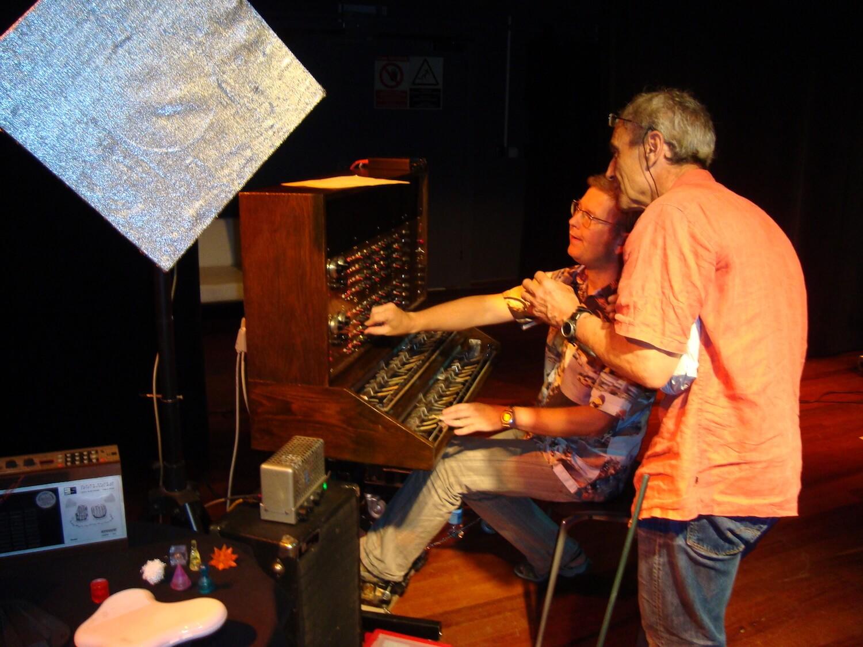 Photographie: scène avec deux musiciens dont un manipule un instrument électronique