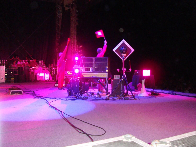 Photographie: scène avec deux musiciens qui manipulent des drapeaux. Lumières de spectacles.
