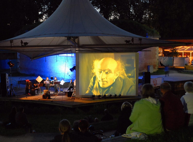 Photographie : sur scène avec quatre musiciens un écran géant avec scène du film Nosferatu. Public en premier plan