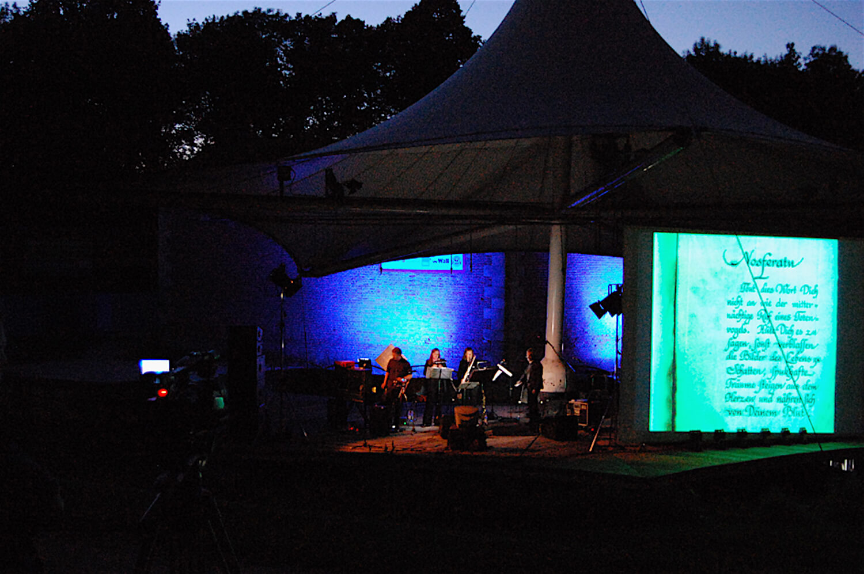 Photographie: sur scène avec quatre musiciens un écran géant avec générique du film Nosferatu. Nuit tombante dans un parc
