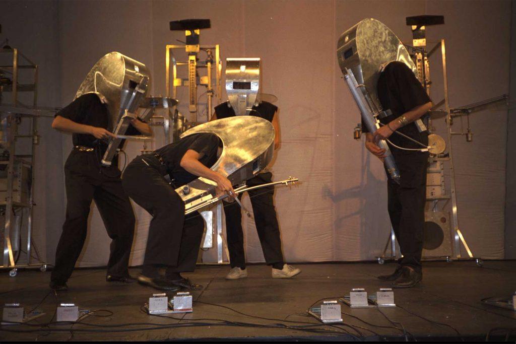 Double Quatuor à Cordes : 4 musiciens portant des masques-intruments en métal jouent devant 4 machines robots à cordes