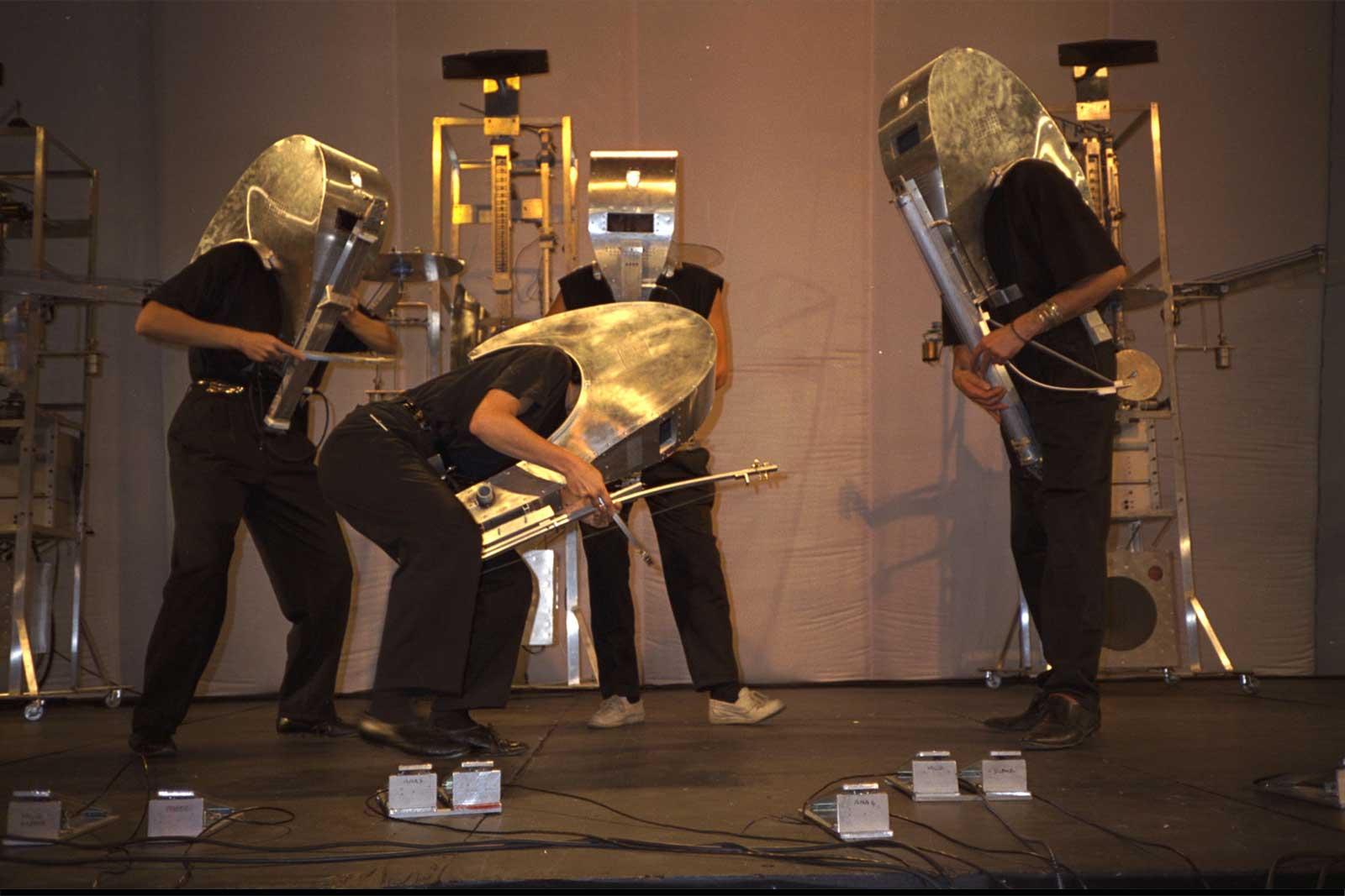 Photographie sur scène, Double Quatuor à Cordes : 4 musiciens portant des masques-intruments en métal jouent devant 4 machines robots à cordes
