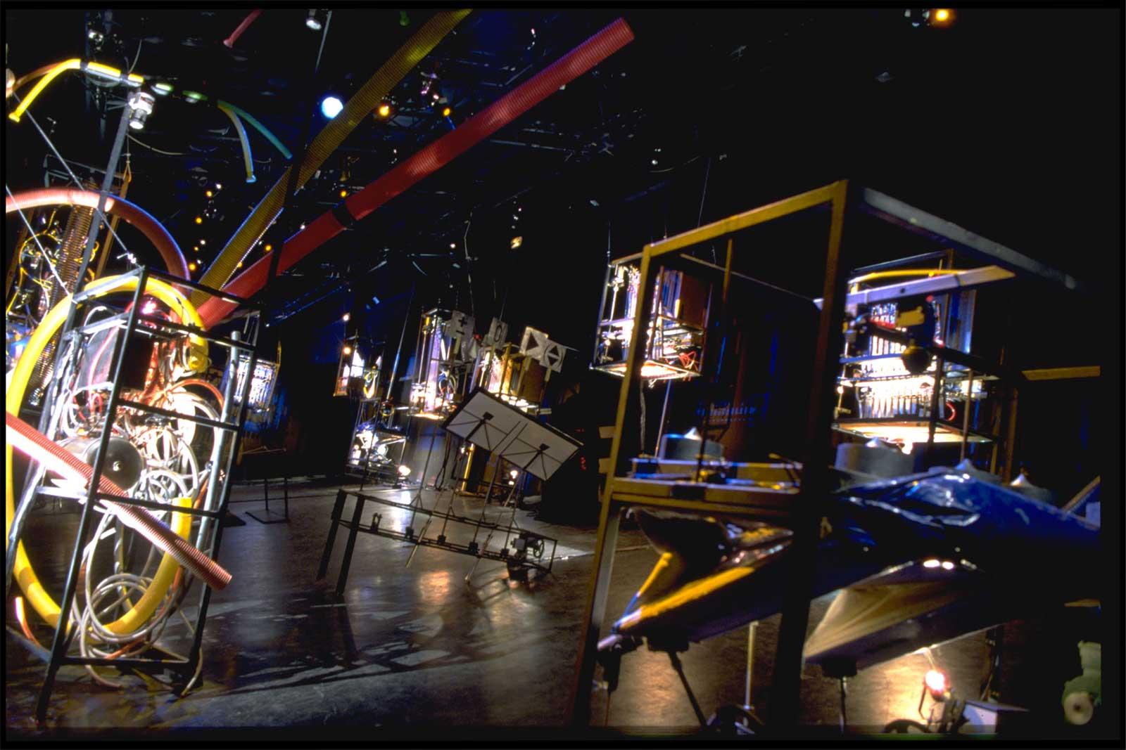 Machines musicales très colorées par les éclairages, sur fond sombre , défiant les lois de la pesanteur.