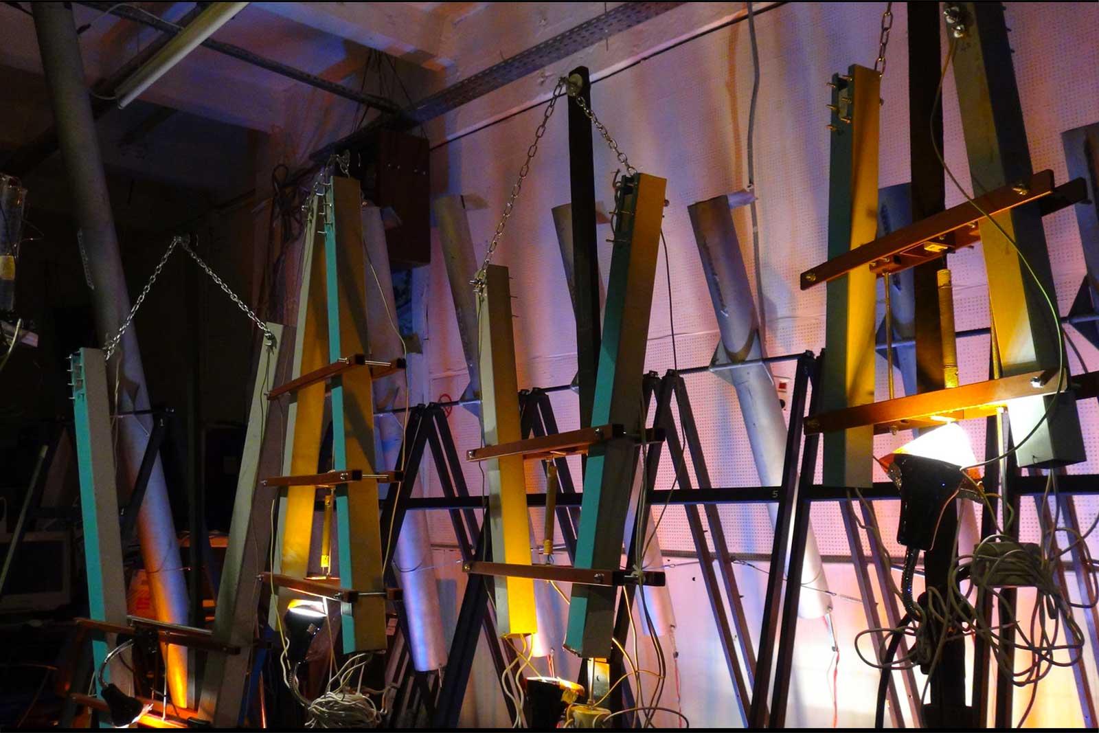 Thermophones verticaux, gris et bleus, colorés par lumières de spectacle sur fond rose-blanc