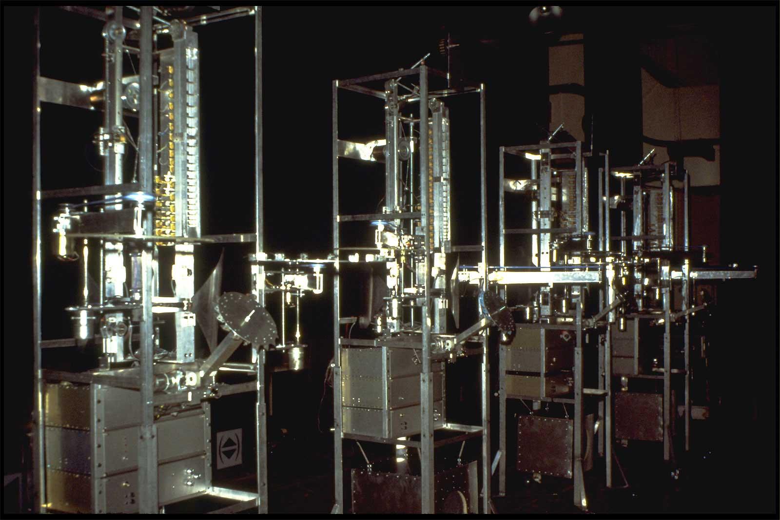 Photographie : 4 structures en aluminium brillant dans la pénombre aves de nombreuses pièces mécanique motorisées
