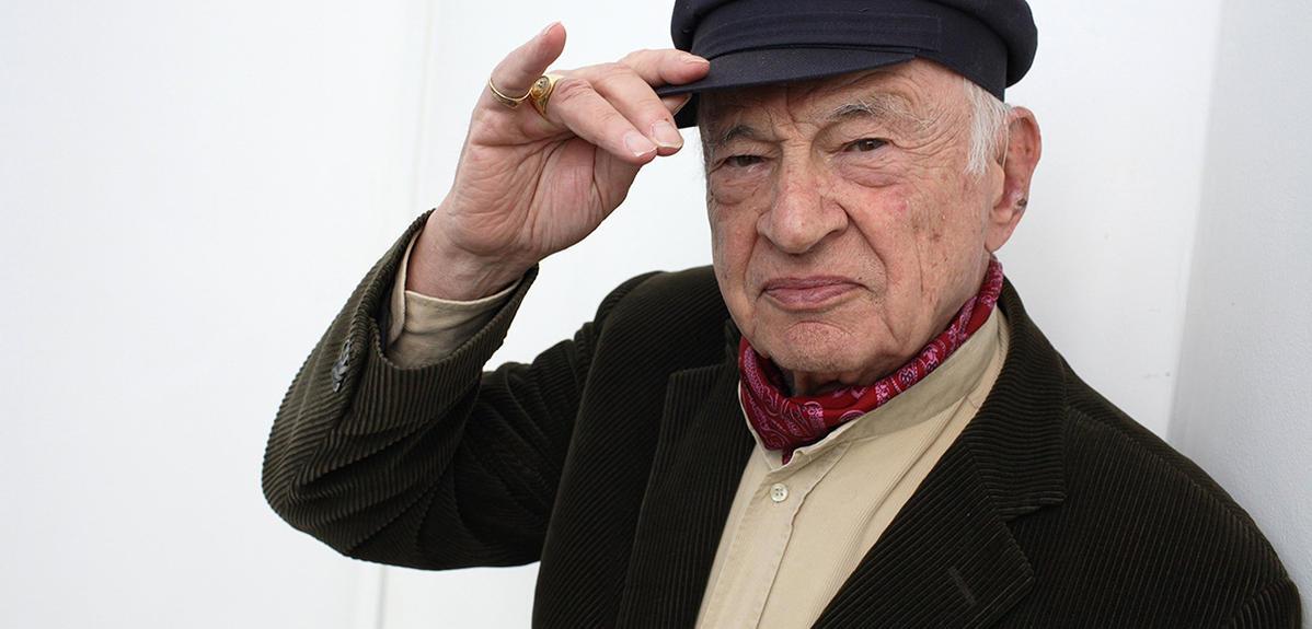 Edgar Morin, souriant fait le geste de retirer sa casquette.