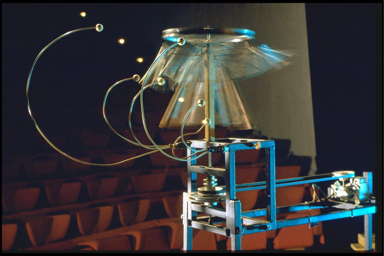 Image métal bleutée sur fond noir. Carillon rotatif frappé par des boules de buis à hauteur différente. Forme évoquant un éléphant mécanique. Sièges de théâtre en fond.