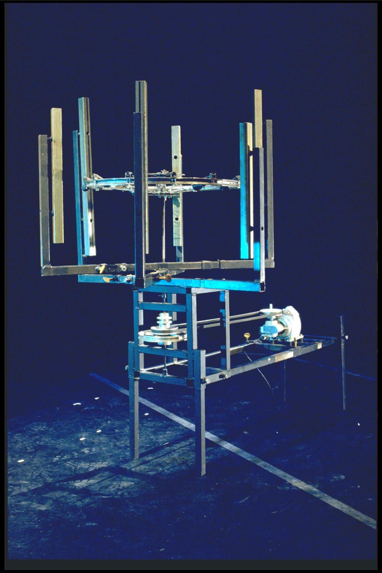 Image métal bleutée sur fond noir. les tubes horizontaux frappés par une roue horizontale évoque un cervidé métallique.