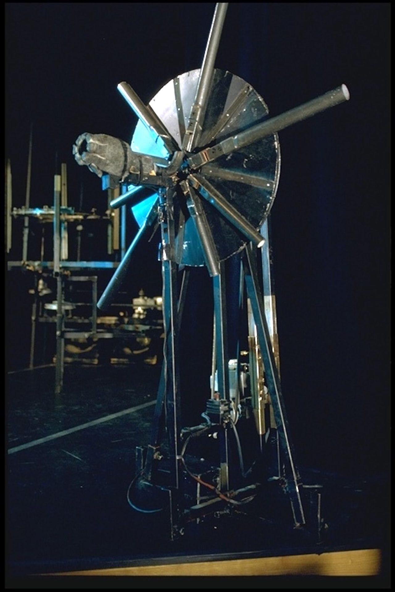 Image métal bleutée sur fond noir. Machine en métal formée d'un disque tournant devant une soufflerie le disque porte des tuyaux d'orgue interchangeables
