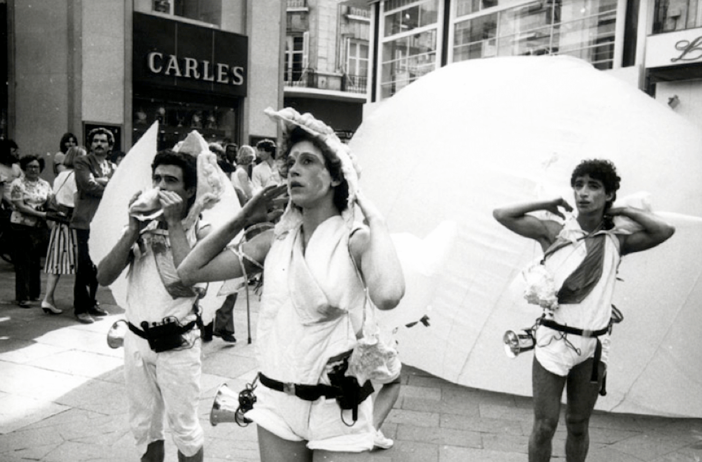 Photographie N&B : deux danseurs et un musicien soufflant dans une conque marine, en costume blanc, se tiennent devant une grosse boule à demi gonflée , le public, en arrière plan les regarde.