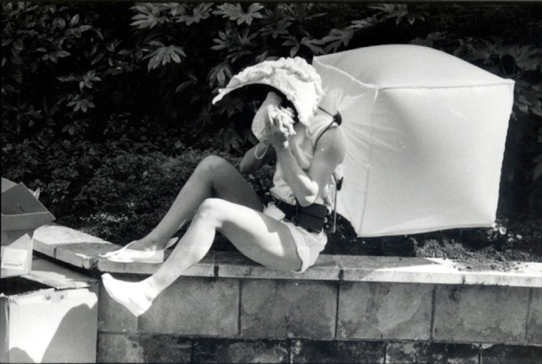 Photographie N&B : une danseuse, allongée-assise sur un bord de mur, habillée en blanc, avec un grand casque coquillage et un grand cube en plastic gonflé dans le dos, joue d'une conque marine