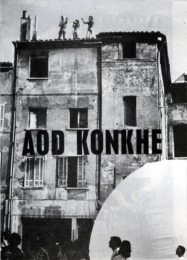 Photographie avec titre AOD KONKHE, public à coté d'un structure gonflable et sur le toit d'un vielle maison de 3 étages, 3 danseurs costumées soufflent dans des conques