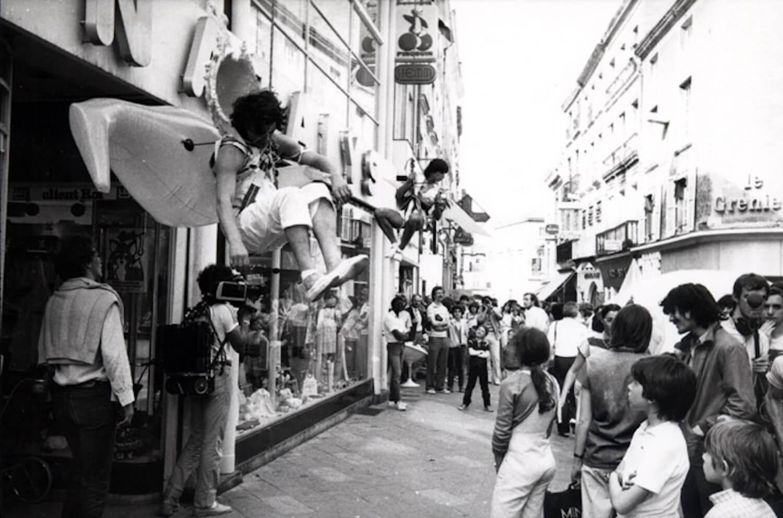 Photographie N&B : dans une ruelle remplie de public deux danseurs, habillés de blanc, avec des structure gonflables, sont accrochés au dessus des gens