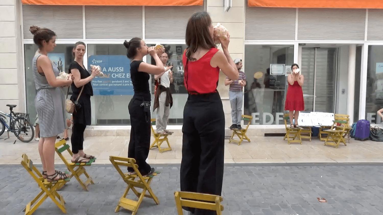 Photographie couleur : dans les rues d'Avignon 4 jeune femme, debout sur des chaises jaunes jouent de la conque marine