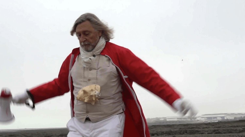 Photographie : un homme, barbu, les bras écartés, avec une combinaison rouge,, un costume blanc et une conque marine à son cou, semble s'envoler en regardant le sol