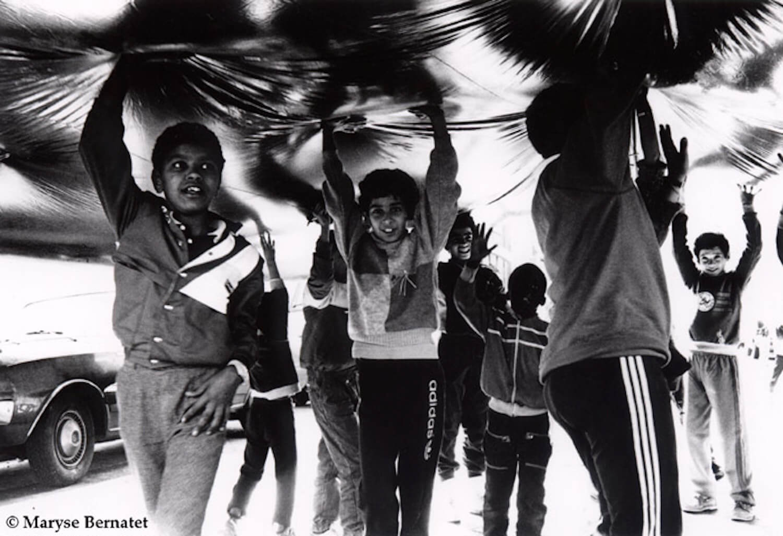 Photographie N&B : une douzaine d'enfants portent à bout de bras une énorme boule gonflable dont on ne voit que le dessous.