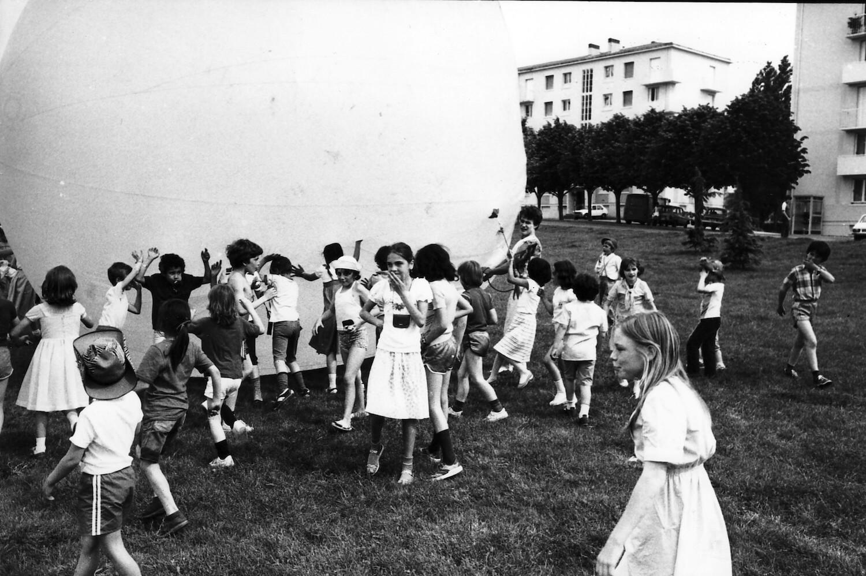 Photographie N&B : une trentaine de jeunes enfants jouent en poussant une boule gonflable de 5 à 6 mètres de diamètre