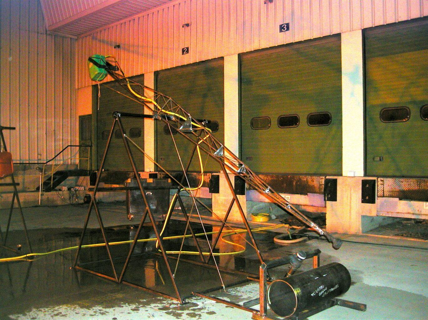 Photographie montrant des structures métalliques articulées de plusieurs mètres de hauteur percutant un gros cylindre métallique horizontal