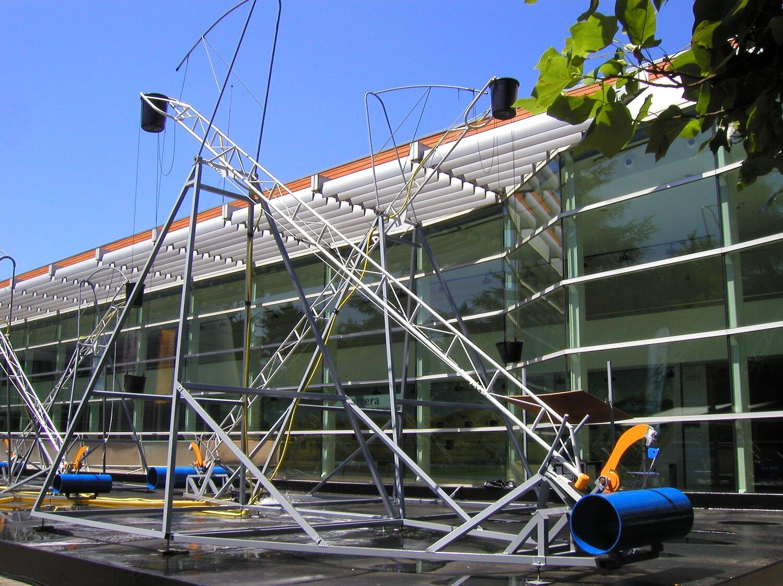 Photographie: devant un bâtiment vitré (musée ) d'un ensemble de sculptures métalliques articulées, de tailles décroissantes, avec à leur base des cylindres bleus et en hauteur un récipent noir