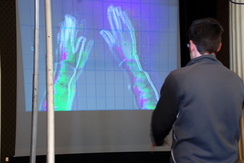 Photographie;: un homme de dos, voit ses mains sur un grand écran devant lui