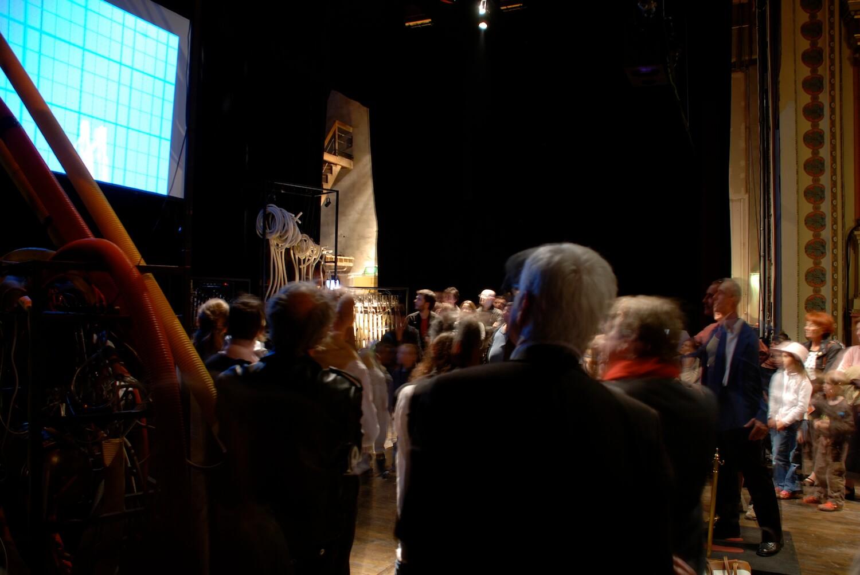 Photographie, sur la scène du théâtre du Pays de Morlaix, le public regarde un grand écran et des machines musicales pilotées par la Camera Musicale