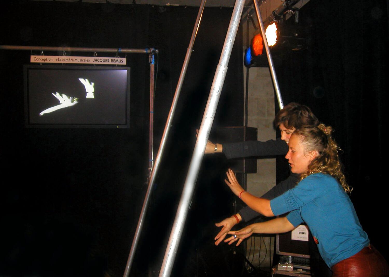 Photographie : deux jeunes femmes, sous un portique, jouent avec leurs mains que l'on voit en N&B sur un écran.
