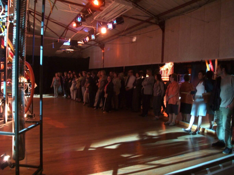 Photographie : public debout pour un concert confidentiel face aux machines et à la cantatrice