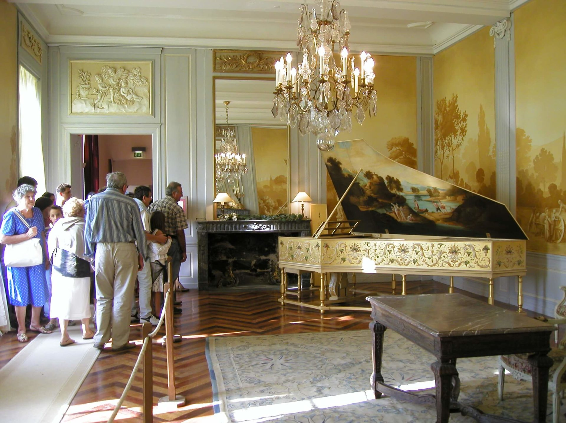 Photographie : derrière un cordon le public écoute le clavecin dans un salle luxueuse 18ème siècle