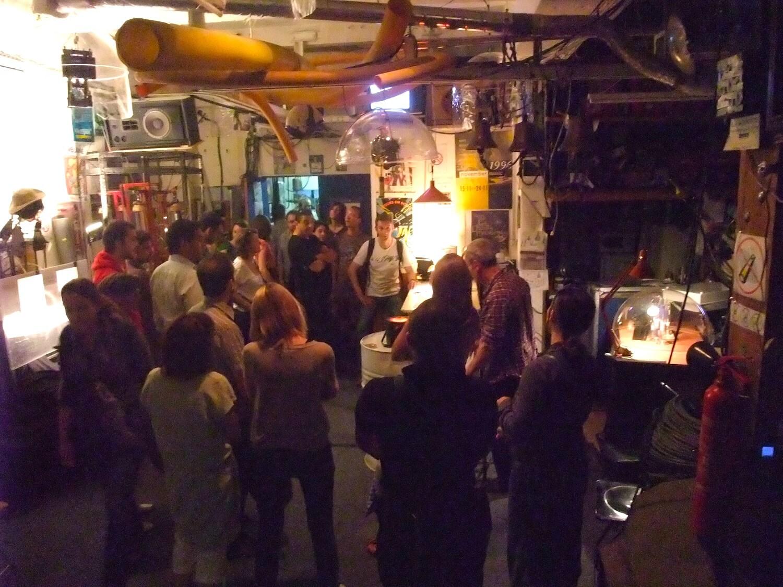 Photographie : public entourant Jacques rémus , le compteur Geiger est au dessus dans une coupelle transparente