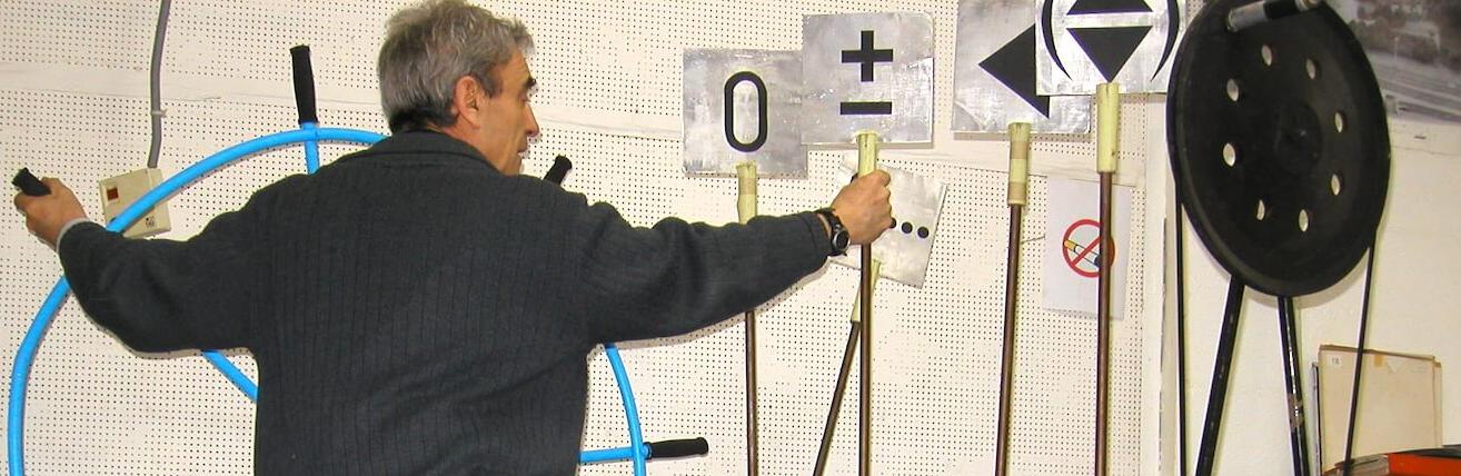 Photographie : homme de dos manipule une grande roue de navire bleue et fait basculer des leviers d'aiguillage portant des symboles