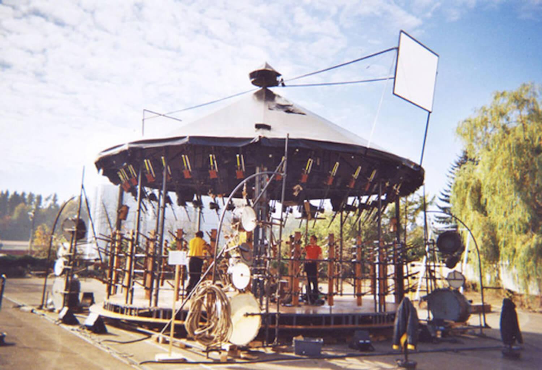 Photographie sur fond de ciel bleu montrant la structure d'un manège mécanique en extérieur avec éléments de percussions et carillon tubulaire, vue en plongée