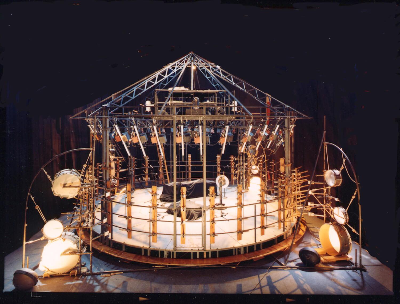 Photographie sur fond noir montrant la structure d'un manège mécanique avec éléments de percussions et carillon tubulaire, vue en plongée